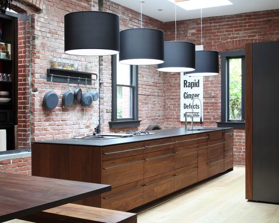 Аскетичный, простой и в то же время необычный дизайн кухни с центральными элементами – деревянным столом и каменной стеной
