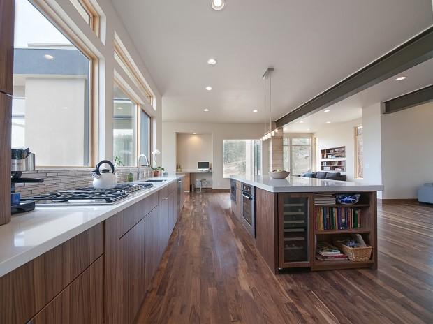 На фото: большая кухня с деревянной мебелью и белой рабочей поверхностью