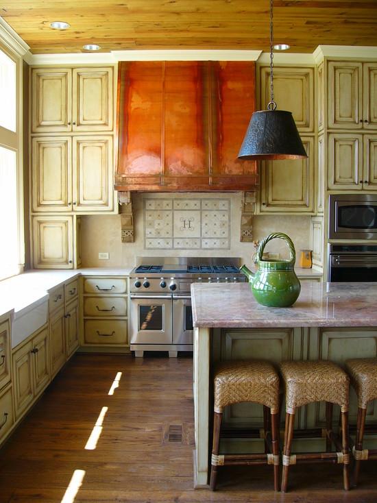 На фото:интерьер кухни с потертым деревом и медной вытяжкой