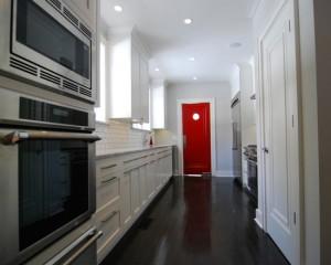 Белая кухня и ярка красная дверь