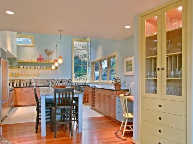 Дерево, а также использование правильно подобранного освещения создают приятную атмосферу в желтой-голубой кухне
