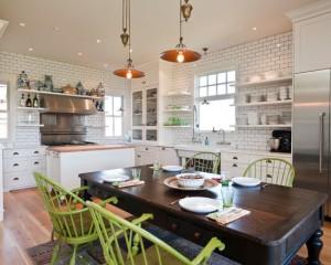 Белая кирпичная кладка с белыми шкафами контрастируют с коричневым столом и зелеными стульями