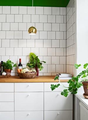 Маленькая золотая люстра над рабочей поверхностью кухни
