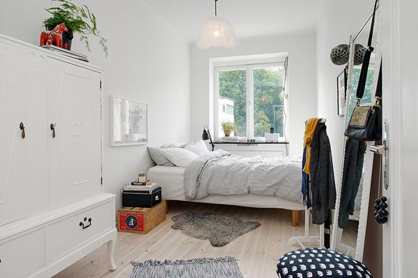 Небольшая вытянутая спальня с стоящим на полу зеркалом