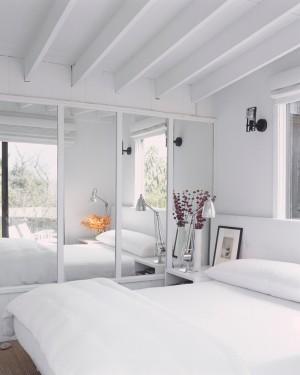 Белая спальня с большим белым зеркальным шкафом