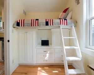 Кровать установлена по верх шкафов для экономии пространства