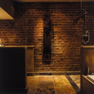 Грубая кирпичная стена в ванной