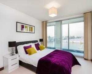 Белое постельное бельё в сочетании с лиловым покрывалом