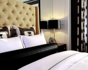 Золотое изголовье кровати и золотая ножка лампы с черным обожаемом