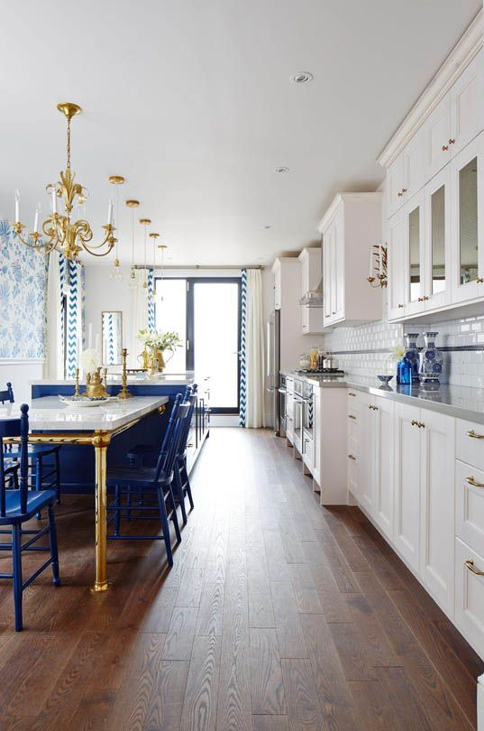 Золотая люстра и основание стола на белой кухне