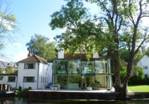 Каменный деревенский дом с стеклянной пристройкой