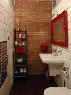 Кирпичная кладка и ярки детали интерьера, делают эту ванную комнату яркой и уникальной