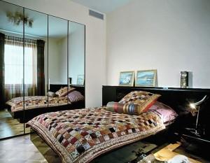 Яркий плед и зеркальный шкаф в небольшой спальне