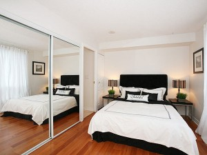 Светлая спальная комната с зеркальным шкафом