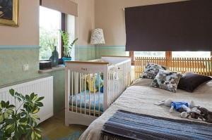 Детская кроватка с высокими перилами рядом с родительской кроватью