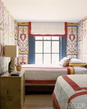 Узкая маленькая спальня с двумя кроватями и пестрыми стенами