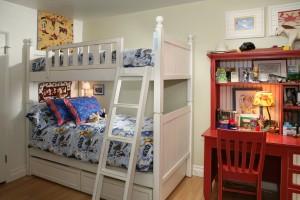 Красный письменный стол рядом с детской кроватью