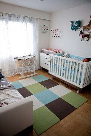 Кроватка у стены, а пеленальный столик у окна