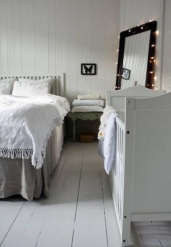 Интерьер в белых тонах в спальне с детской кроваткой