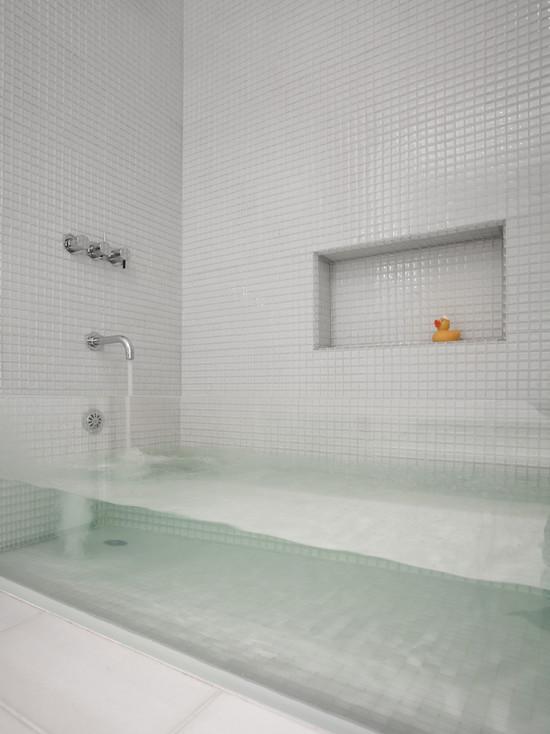 Стеклянная ванна в белой ванной комнате