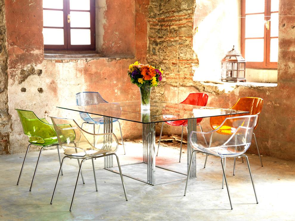 Разноцветные прозрачные стулья вокруг стеклянного стола