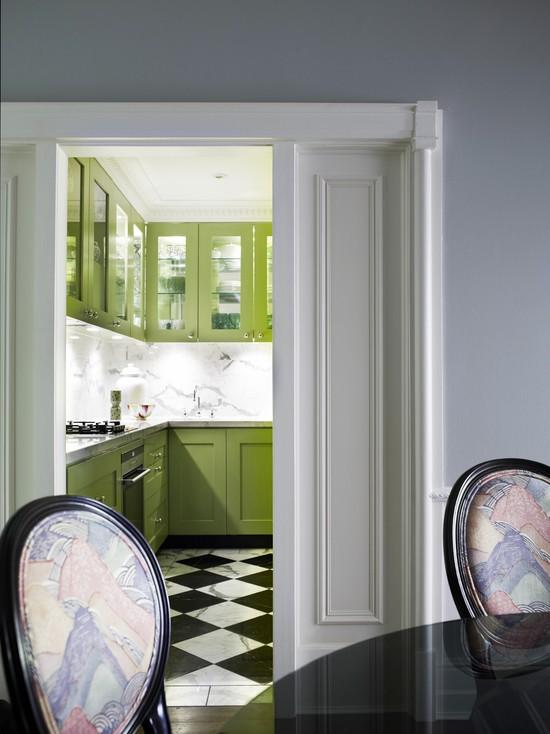Черная плитка на полу хорошо гармонирует с зеленой кухней
