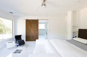 Use-of-barn-door-adds-warmth-to-the-minimalist-room-in-white